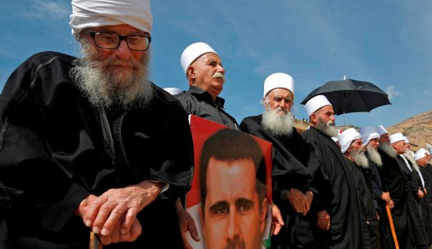Elderly members of the Druze community stand holding a portrait of Syrian President Bashar al-Assad, October 6, 2018