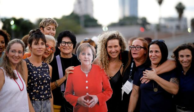 A group of working women in the Israeli high-tech industry pose with a cardboard cutout of German Chancellor Angela Merkel during a protest at Rabin Square in Tel Aviv, Israel October 10, 2018.