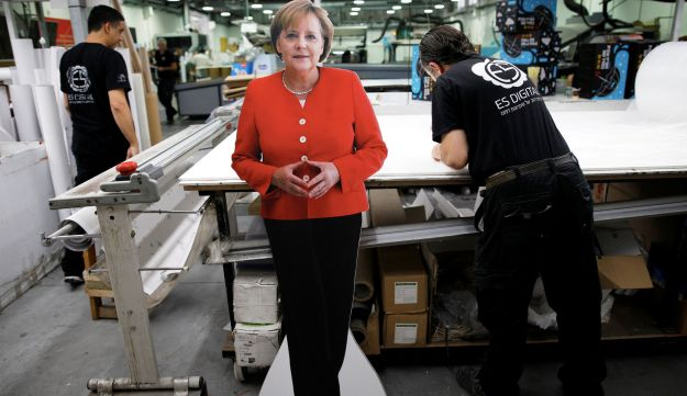Employees work near a cardboard cutout of German Chancellor Angela Merkel, which will be used in a protest held by working women in Israeli high-tech companies, at a printing shop in Yavne, Israel October 9, 2018. Picture taken October 9, 2018.