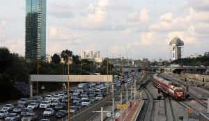 Cars drive on a highway as a train enters a station in Tel Aviv, Israel November 25, 2018.