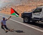 A Palestinian a  national flag next to an Israeli police vehicle during a demonstration against the
