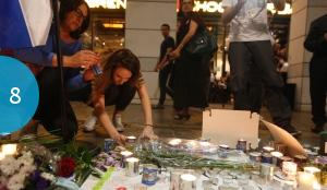 Israelis light candles outside the cafe where a terror attack claimed the lives of four people.